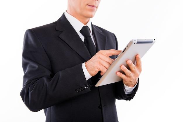 Человек в черном костюме читает новости на планшете