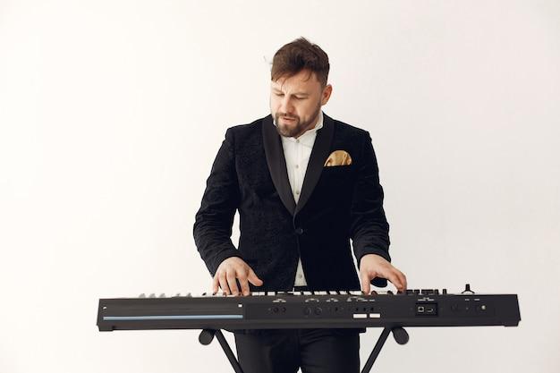 Человек в черном костюме стоит с электро клавиатурой