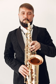 Человек в черном костюме стоит с саксофоном