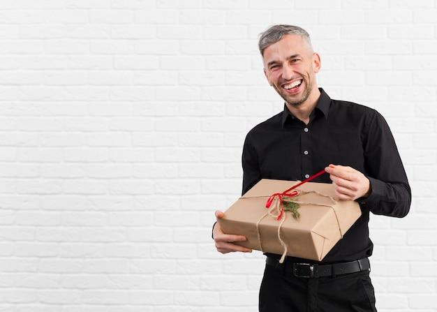 Мужчина в черном костюме распаковывает подарок и улыбается