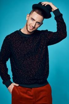ファッションスタジオの青い背景をポーズ黒のセーターキャップの男