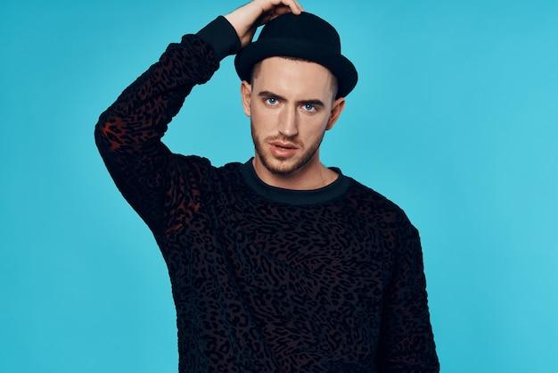 패션 스튜디오 파란색 배경 포즈 검은 스웨터 모자에 남자