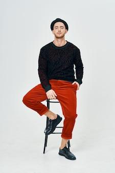 スタジオの自信を持ってポーズをとる黒いセーターの赤いズボンの男