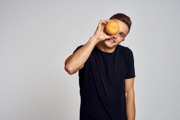 オレンジダイエット食品のライフスタイルを保持している黒のtシャツの男。