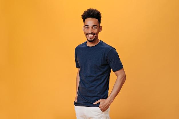 Человек в черной футболке сладко улыбается на оранжевой стене