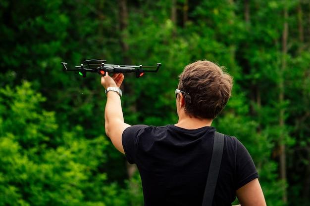 Человек в черной футболке запускает дрон в небо в лесу