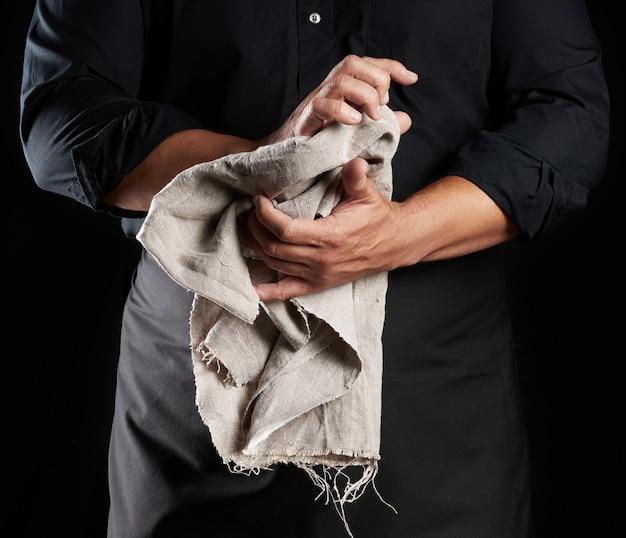 黒い制服を着た男が灰色の麻布を保持し、彼の手を拭く、シェフが黒い背景の上に立つ、クローズアップ