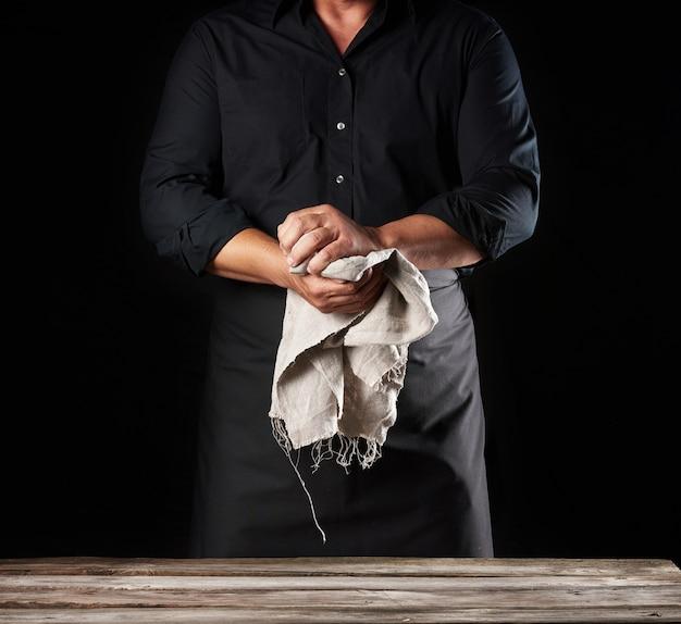 Человек в черной форме держит серую льняную тряпку и вытирает руки