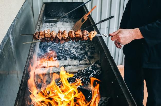 검은 제복을 입은 남자가 그릴에 고기 돼지고기를 튀기고 있습니다. cook은 여름 파티를 위해 시시 케밥을 만들고 있습니다. 나무 패널에 shashlik 및 화재.