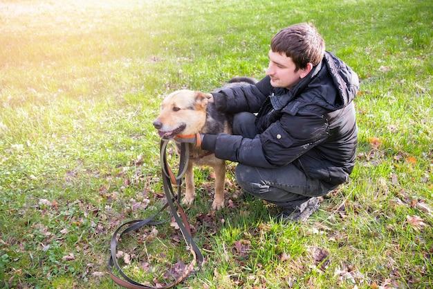 太陽に照らされた緑の芝生のフィールドに茶色の犬と黒の男。