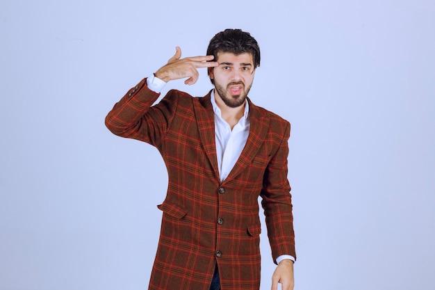 손에 총 기호를 만드는 재킷에 남자.
