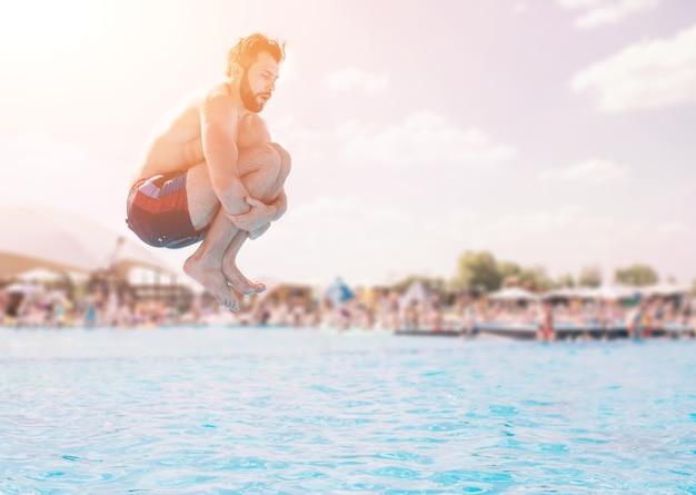 Человек в синих и красных шортах прыгает в бассейне в солнечный день