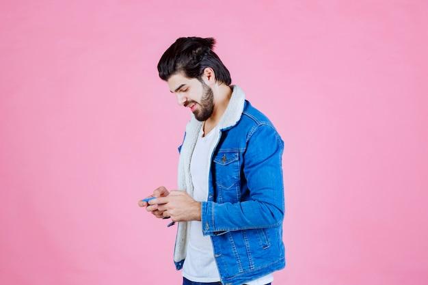 Человек в синей куртке писать сообщение или комментировать по телефону.