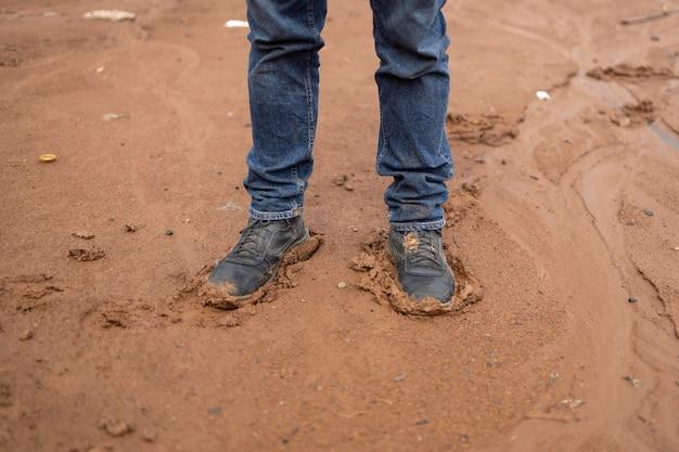 泥の中に立っているブルージーンズと黒い靴の男