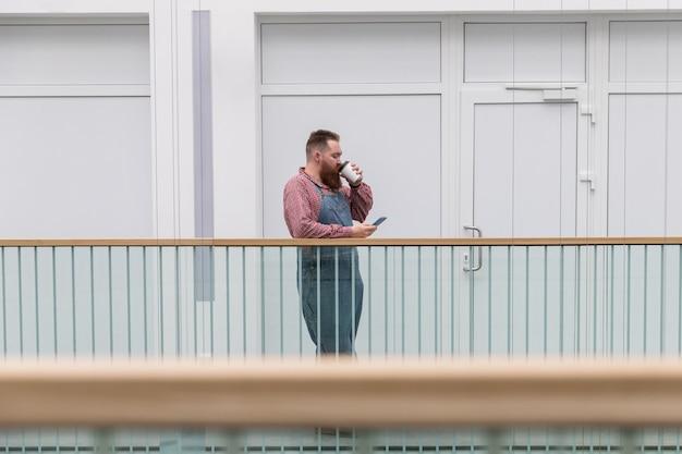 Человек в синем комбинезоне пьет кофе во время использования смартфона