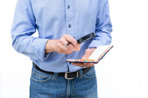 青いシャツと青いズボンの男が虫眼鏡で紙のノートを調べています。白い背景の上の写真。スペースをコピーします。