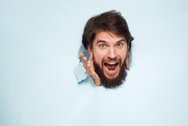 青いシャツを着た男が背景のオフィスのクローズアップを突破