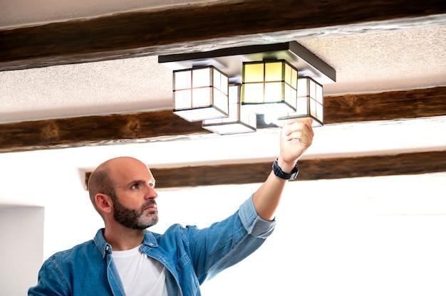 Человек в синей рубашке меняет лампочки дома