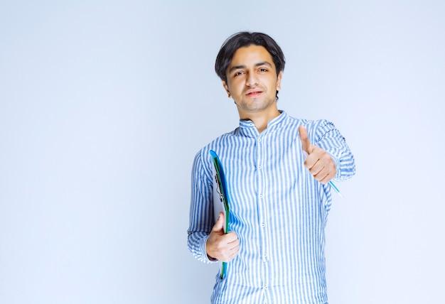 녹색보고 폴더를 들고 파란색 셔츠에 남자입니다. 고품질 사진