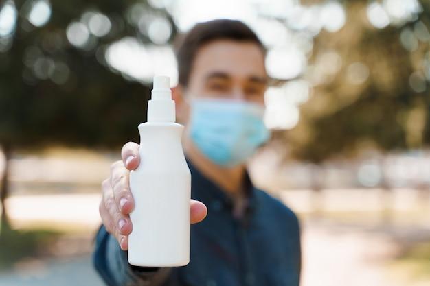 Мужчина в синей стерильной медицинской маске показывает белую пластиковую бутылку с антисептиком