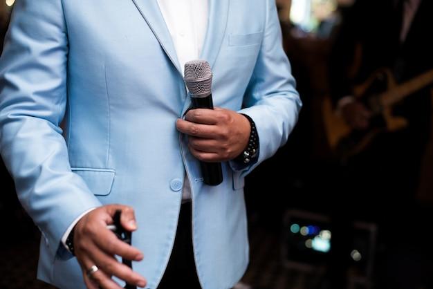 Мужчина в синем костюме держит микрофон
