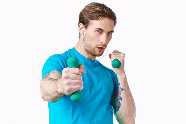 手タトゥーフィットネストレーニングでダンベルと青いtシャツの男