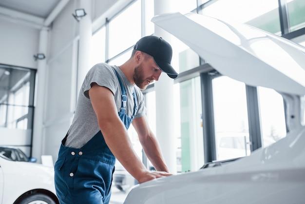 Человек в синей форме и черной шляпе ремонтирует поврежденный автомобиль.
