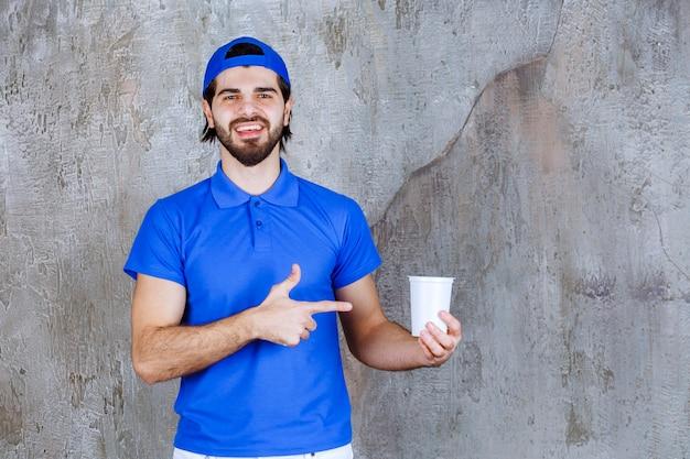 持ち帰り用の飲み物を持っている青い制服を着た男。
