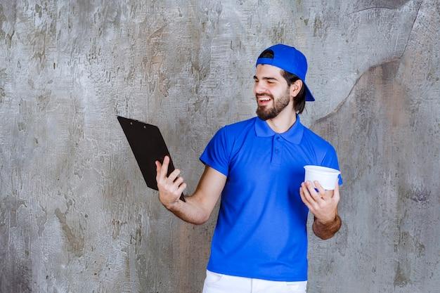 파란색 유니폼을 입은 남자가 테이크아웃 플라스틱 컵을 들고 고객 이름을 읽고 있습니다.