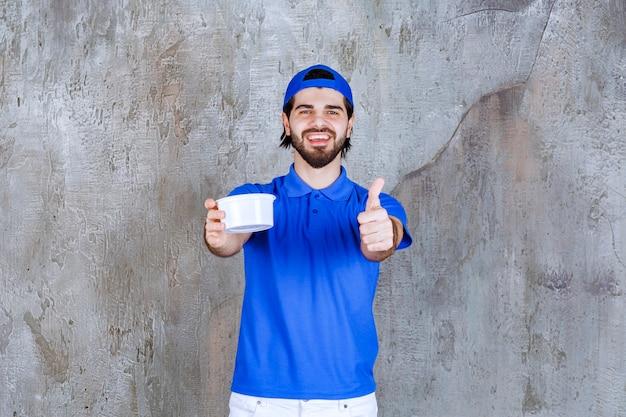 파란색 유니폼을 입은 남자가 테이크아웃 플라스틱 컵을 들고 긍정적인 손 기호를 보여줍니다.