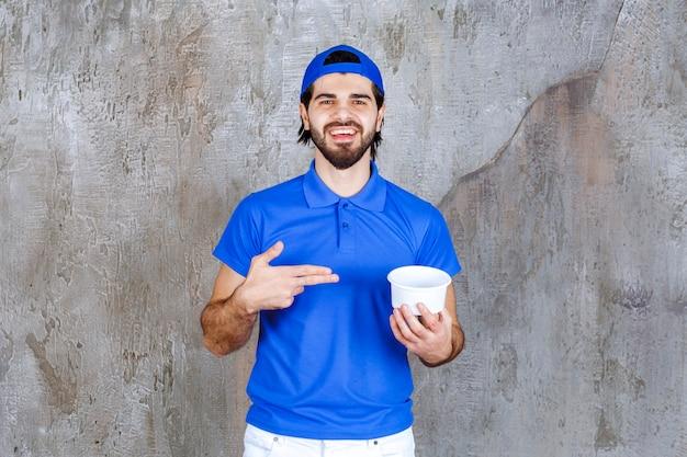 테이크아웃 플라스틱 컵을 들고 파란색 유니폼을 입은 남자