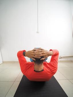 파란색 무선 헤드폰을 끼고 체육관 매트에 누워 복근 운동을 하는 남자. 뒷모습.