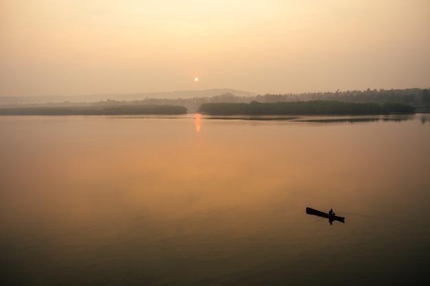 Человек в лодке на озере на закате (рассвет)