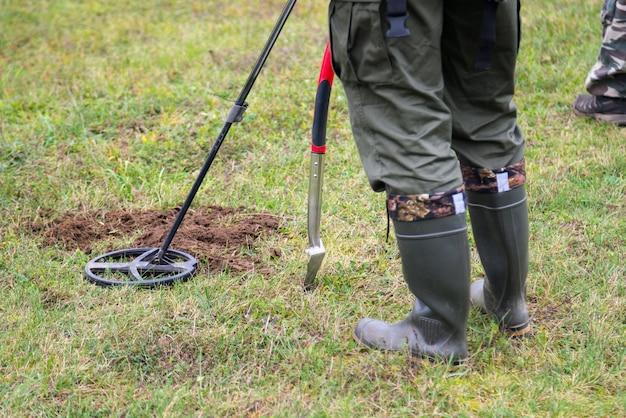ブーツを履いた男が屋外の芝生で金属探知機を使って宝探しをしています。