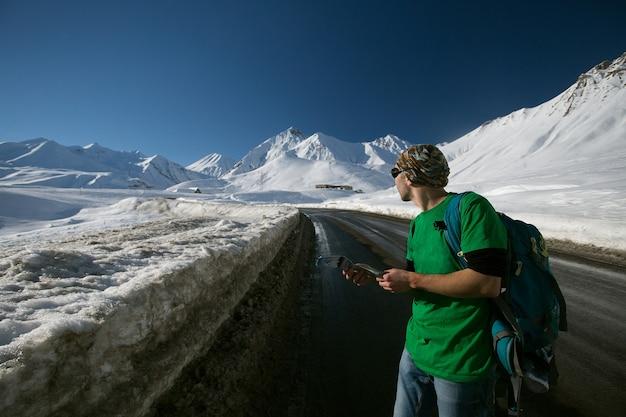 Человек в яркой спортивной одежде и солнцезащитных очках с рюкзаком, путешествующий по заснеженным горам в грузии. человек смотрит на карту космоса. индивидуальный путешественник и концепция зимнего побега