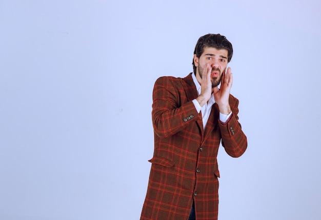 손으로 그의 얼굴을 닫는 갈색 재킷에 남자.