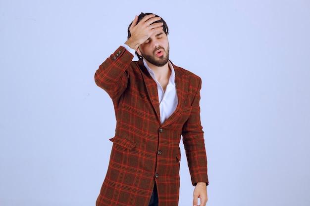 갈색 재킷을 입은 남자는 아프거나 아프다고 느낍니다.