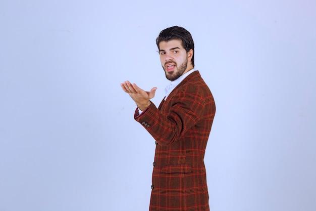 Человек в коричневом пиджаке разговаривает с широко раскрытыми руками.