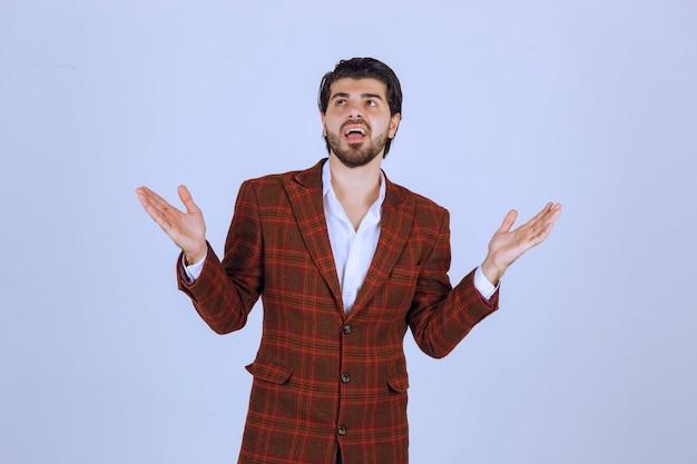 手を大きく開いてスピーチをしている茶色のブレザーの男。