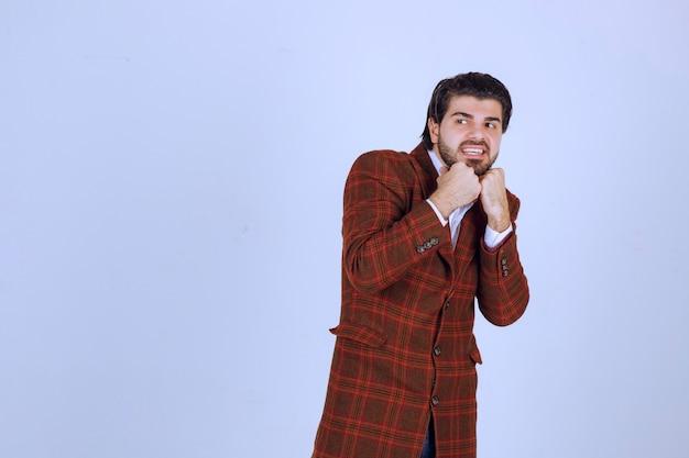 갈색 재킷을 입은 남자는 두렵고 무서워 보입니다.