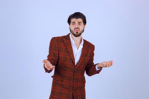 갈색 재킷을 입은 남자는 혼란스럽고 자신을 설명하려고합니다.