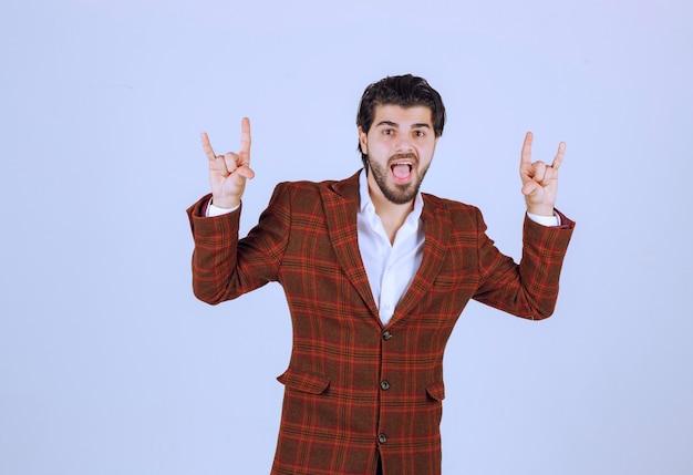 손 기호를 만들고 춤을 갈색 재킷에 남자.