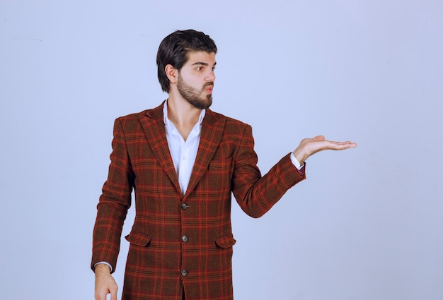 오른쪽을 가리키고 말하는 갈색 재킷을 입은 남자.