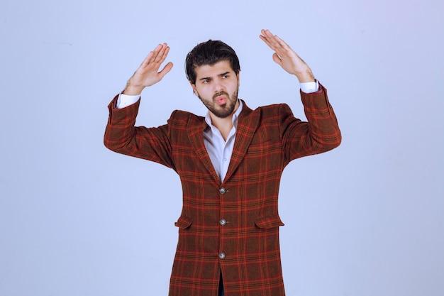 거대한 무언가를 가리키는 갈색 재킷을 입은 남자.