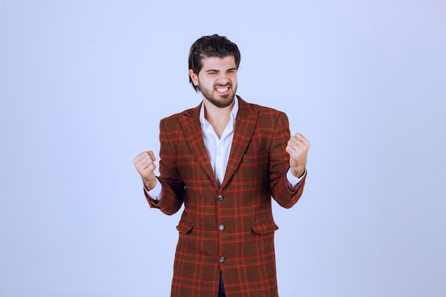 Мужчина в коричневом пиджаке показывает кулаки и чувствует высокую мотивацию.