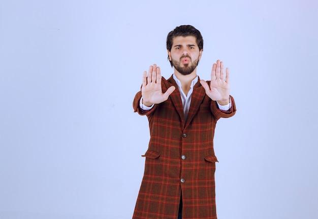 갈색 재킷을 입은 남자가 무언가를 멈추고 피하려고합니다.