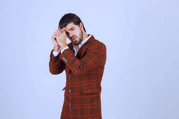 Мужчина в коричневом пиджаке складывает ладони и о чем-то просит.