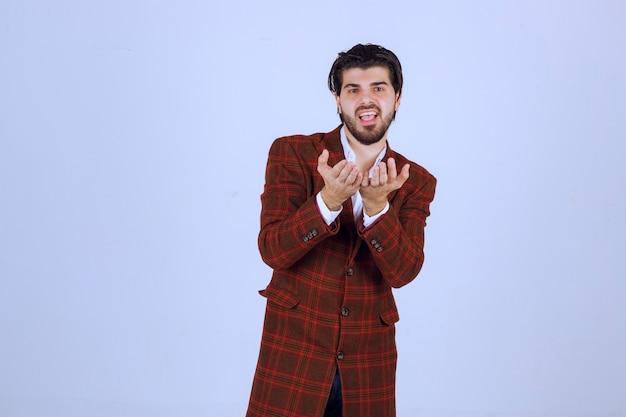 観客に愛を吹く茶色のジャケットの男。