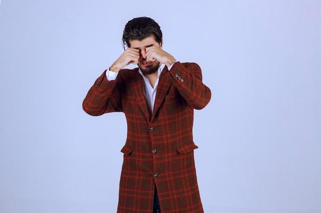 目を閉じて眠そうな茶色のジャケットを着た男。
