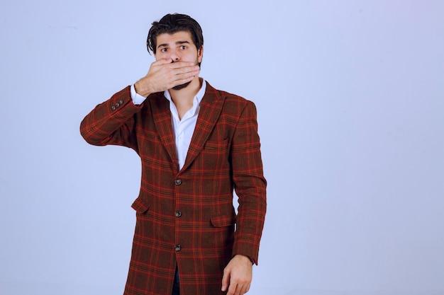 손으로 그의 얼굴을 숨기고 갈색 재킷에 남자.